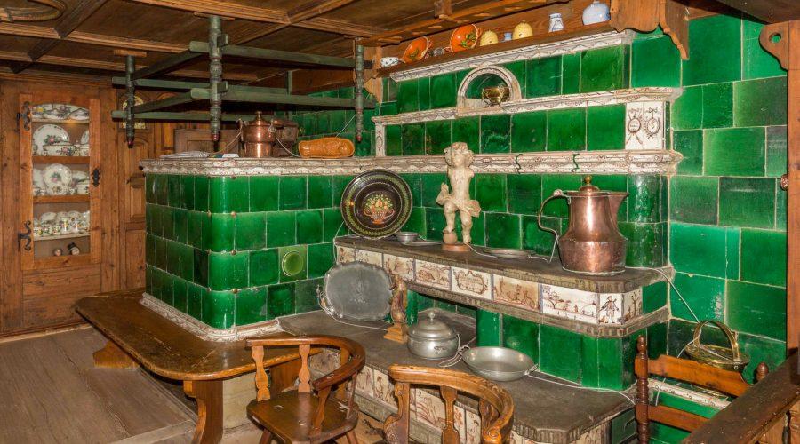 """Heimatmuseum Hüsli: Die """"Chust"""" (""""Kunscht"""", der Kachelofen mit geheizten Bänken) steht im Eßzimmer. Sie stammt aus einer Mühle in Kutterau bei St. BLasien. Die blanken, grünglasierten Kacheln werden von weißen Gesimsen und Bilderfriesen mit feinen lustigen Zeichnungen gerahmt. Die barocke """"Täfer"""" Decke stammt aus einem Hof im Erlenbachtal bei Rothaus un d das Büfettli im Hintergrund aus Gündelwangen."""